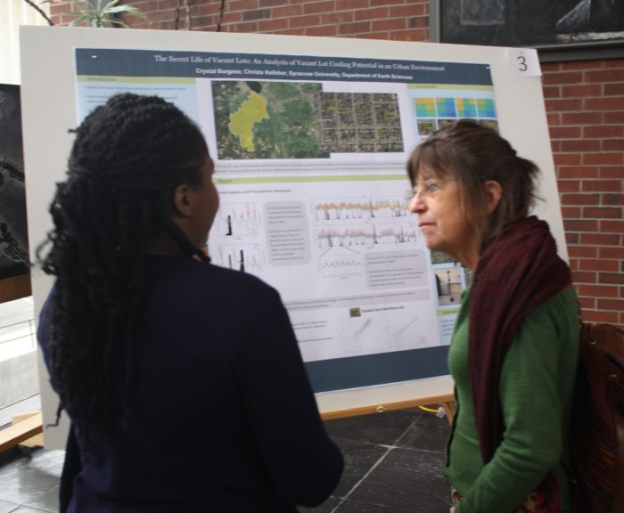 Dr. Lisa Morgan speaking with graduate student about her research poster