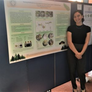 WiSE summer research scholar stands next to her poster